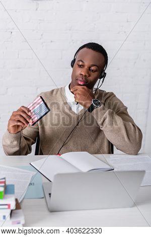 Thoughtful African American Interpreter In Headset Holding Digital Translator With Usa Flag Emblem N
