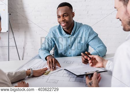 Interpreter Holding Contract And Pen While Woman Giving Bribe To Happy African American Businessman