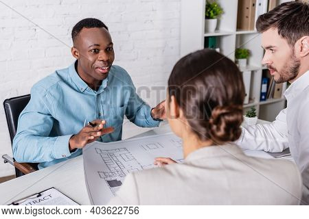 Excited African American Businessman Gesturing While Talking To Business Partner And Interpreter Nea