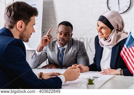 Cheerful Arabian Businesswoman Looking At Interpreter Near African American Businessman Showing Idea