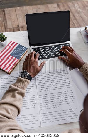 Cropped View Of African American Interpreter Translating Documents Near Laptop And Dictionary With U