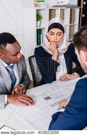 Serious Multiethnic Business Partners Looking At Blueprint Near Interpreter, Blurred Foreground