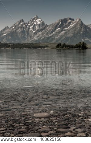 Edge Of Jackson Lake With Grand Teton Blurred In Background From Hermitage Point