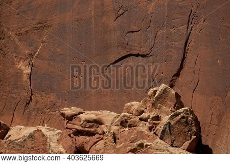 Goat Figure Petroglyphs Carved Into Dark Stone Wall In Capitol Reef National Park