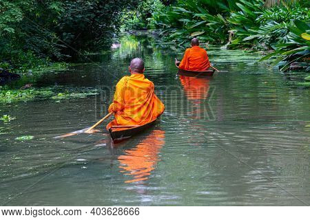 Buddhist Monks Paddle Boat In The Canal. Two Monks Row The Small Wooden Boat In A Canal To Receive A