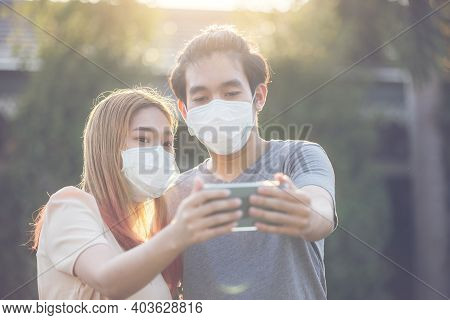 Asis Couple  In Medical Masks Making Selfie With Phone