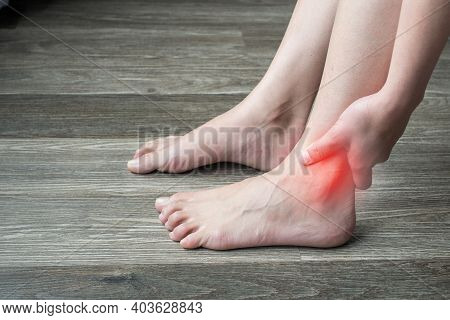 Close Up Of Woman Hands Holding And Touching Her Ankle, Suffering From Ankle Pain. Ankle Pain May Be