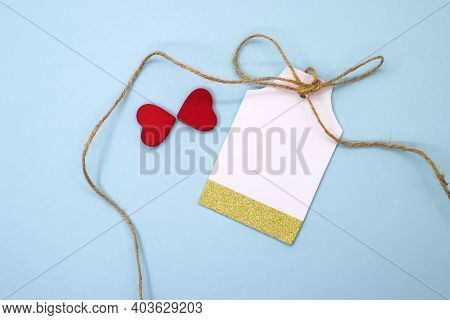 On A Blue Background A Gift Label Or Tag For The Price Tag Next To Two Red Hearts. The Concept Of Ho