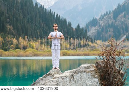 Young Zen Man In Meditation. Outdoor Yoga In Mountain Lake