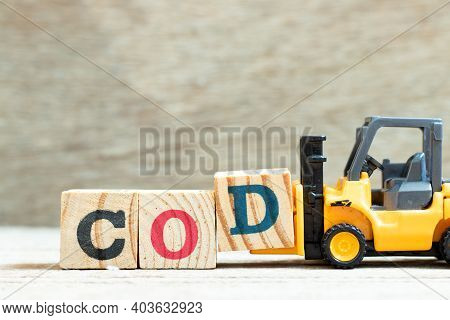 Toy Forklift Hold Letter Block D To Complete Word Cod (abbreviation Of Cash On Delivery) On Wood Bac