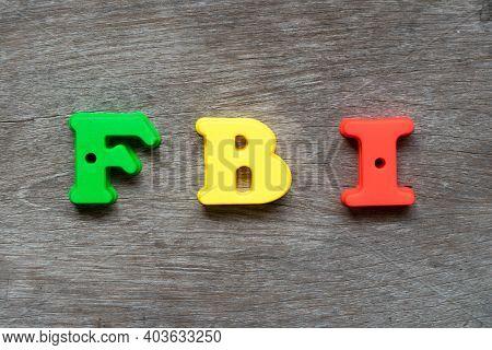 Colorful Plastic Alphabet In Word Fbi (abbreviation Of Federal Bureau Of Investigation) On Wood Back