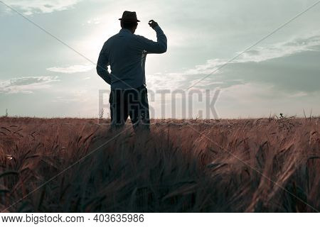 A Man In A Hat Stands On The Field During Dawn With His Back To Us. A Look Into The Future To Meet A