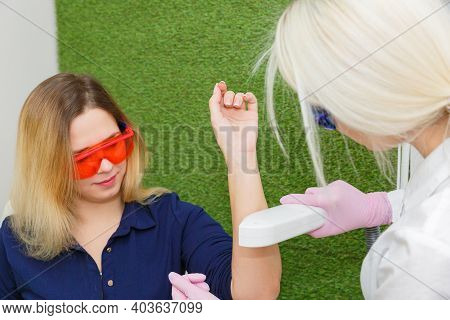A Hair Removal Specialist Performs Laser Depilation On A Young Womans Arm.