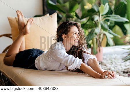Home Lifestyle Woman Relaxing Enjoying Luxury Sofa On Outdoor Patio Living Room. Young Female Sittin