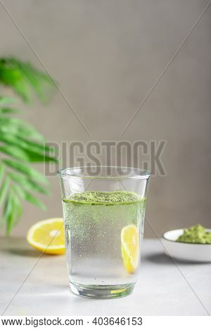 Glass Of Water With Green Superfood Powder. Healthy Drink To Support Immunity And Digestive Health.