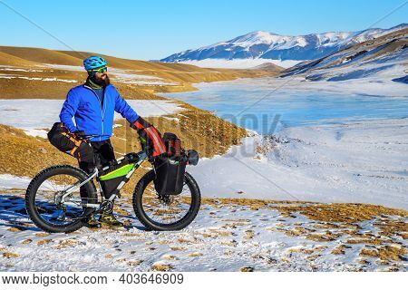 Bearded Male Traveler On A Bicycle In Winter In The Mountains. Winter Travel. High-mountain Plateau