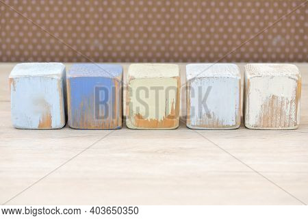 Wooden Blocks On A Wooden Surface And A Brown Background.