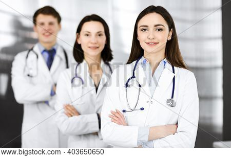 Group Of Young Professional Doctors Is Standing As A Team With Arms Crossed In A Hospital Office And