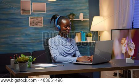 Portrait Of Happy Smiling Black Designer Woman With Headphones Sitting At Home Office Desk, Working