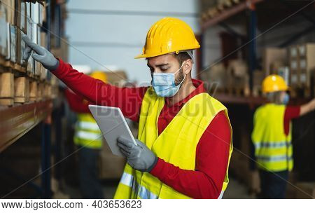 Young Man Working In Warehouse Doing Inventory Using Digital Tablet And Loading Delivery Boxes Plan