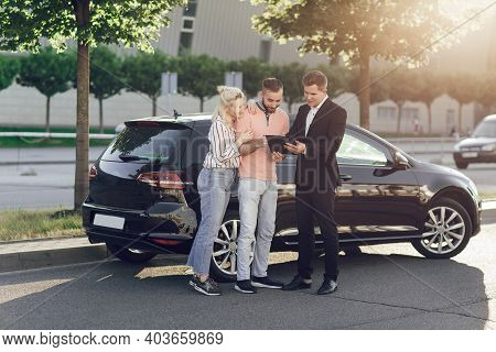 A Young Salesman Shows A New Car To Customers. Happy Couple, Man And Woman Buy A New Car. Young Peop