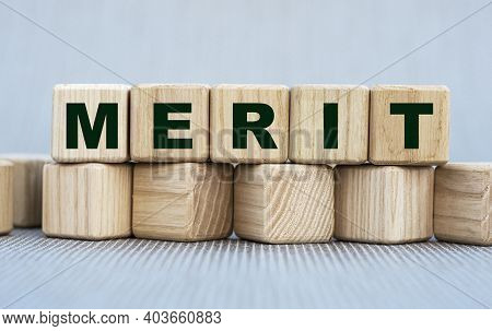Merit - Word On Wooden Cubes On A Beautiful Gray Background. Business Concept