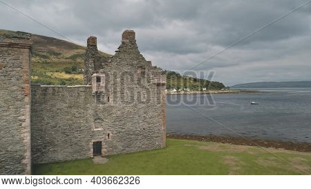 Closeup of ancient castle ruins at sea bay aerial. Nobody nature seascape with boats. Historic heritage. Hamilton dynasty palace on ocean coast of Arran Island, Scotland, UK, Europe. Drone shot