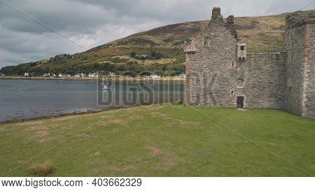 Closeup castle walls ruins at seascape aerial. Historic British palace of Hamilton dynasty. Green grass valley and mountain at sea coast of Loch-Ranza, Arran Island, Scotland, United Kingdom, Europe