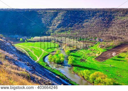 Green Riverside Valley . Spectacular Spring Landscape . Flowing River And Green Meadows With Hills S