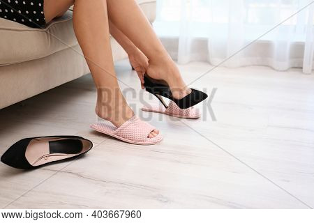 Woman Taking Off Uncomfortable Shoes And Putting On Soft Slippers At Home, Closeup. Tired Feet After