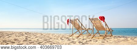 Sun Loungers With Santa's Hats On Beach, Banner Design. Christmas Vacation