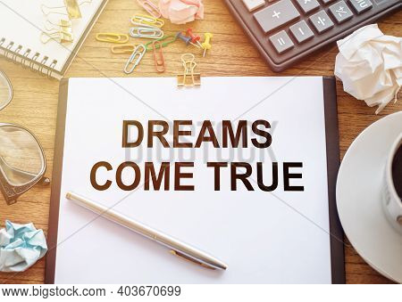 On A Wooden Table There Is An Office Sheet Of Paper With The Text Dreams Come True. Business Workspa