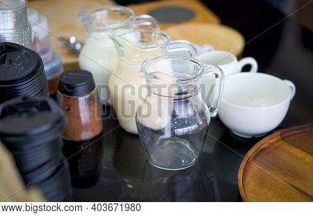 Various Essential Components For Making Coffee Are Placed On The Granite Countertop. Fresh Milk, Con