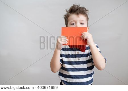 Cute Boy In Bow Tie With Red Envelope Near Face. Valentine Day.
