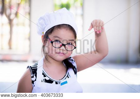 Child In Cooking Clothes Is Raising His Hand In Sprinkle Salted Pose. Girl Wearing Glasses. Children