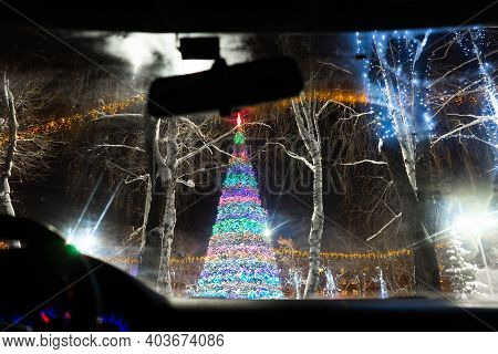 A View Through A Car Glass Of A Large Christmas Tree Decorated With Lights. View From The Inside Of