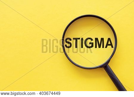 The Word Stigma Is Written On A Magnifying Glass On A Yellow Background.