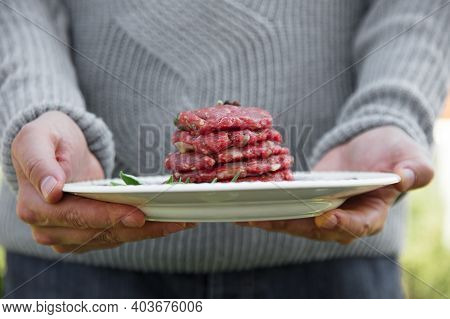 Man Is Holding Burgers For Bbq. Barbecue Burgers