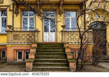 Facade Of Renovated Tenement House With Old Stairs And Terrace
