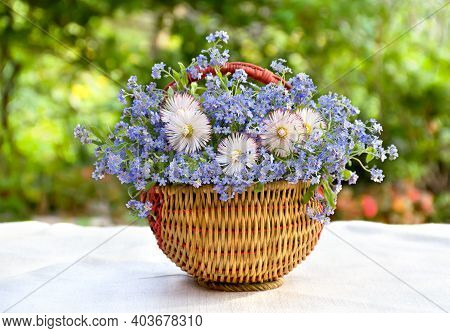 Bouquet With Marguerite And Forget-me-not In The Basket On Table