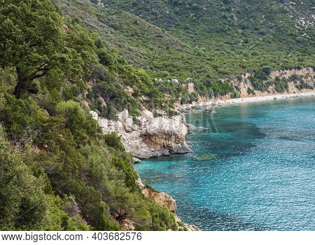 View Over Gulf Of Orosei From Pedra Longa With Limestone Cliffs, Green Bushes And Turquoise Blue Wat