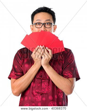 Shocked Asian Chinese man holding many red packets / ang pow  for happy chinese new year, isolated over white background