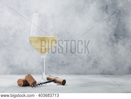 Glass Of Summer White Wine With Corks And Corkscrew On Light Table Background.