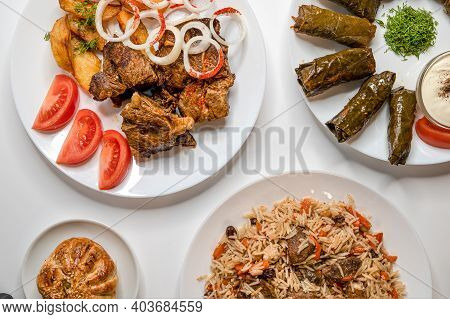 Top View Of Kazan Kabob, Plov, Dolma And Fried Chicken. Uzbek Main Dishes On White Plates.