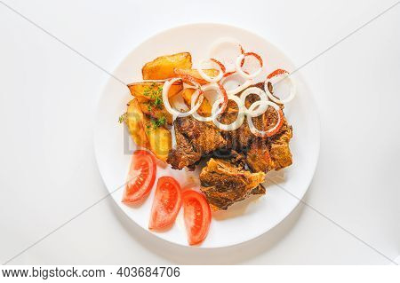 Top View Of Delicious Uzbek Dish Of Lamb Stew With Potatoes And Vegetables On A White Plate. Kazan K