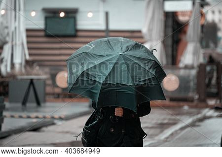 Woman Walking In The City With Green Umbrella On Rainy And Windy Day.
