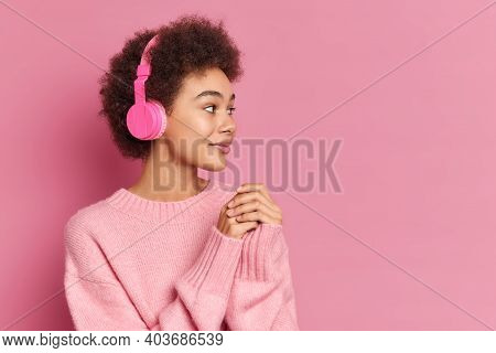 Horizontal Shot Of Pretty Curly Haired Ethnic Woman Wears Stereo Headphones On Ears Concentrated Asi
