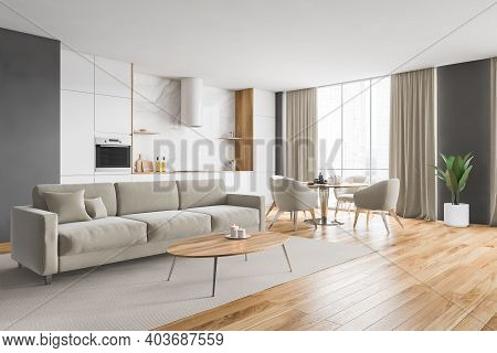 Wooden And Beige Minimalist Kitchen Set Near Window With Curtains. Sofa And Dining Table With Dishes