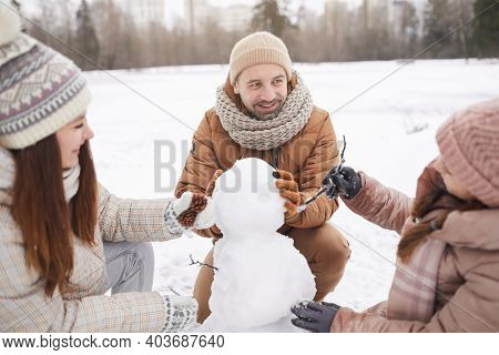 Portrait Of Happy Family Building Snowman Together While Enjoying Winter Vacation Outdoors, Focus On