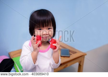 Cute Asian Girl Playing With Orange-red Square Blocks Wooden. Mobile Phones Placed On Wooden Tables.